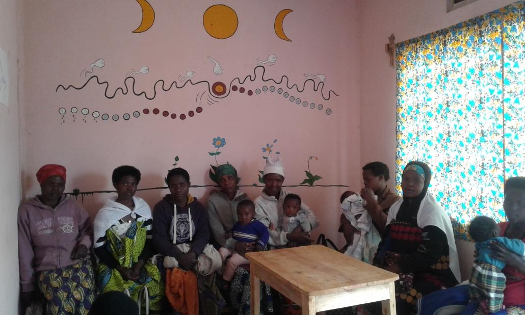 Die Mütter sitzen vor dem Wandbild des Menstruationszyklus.