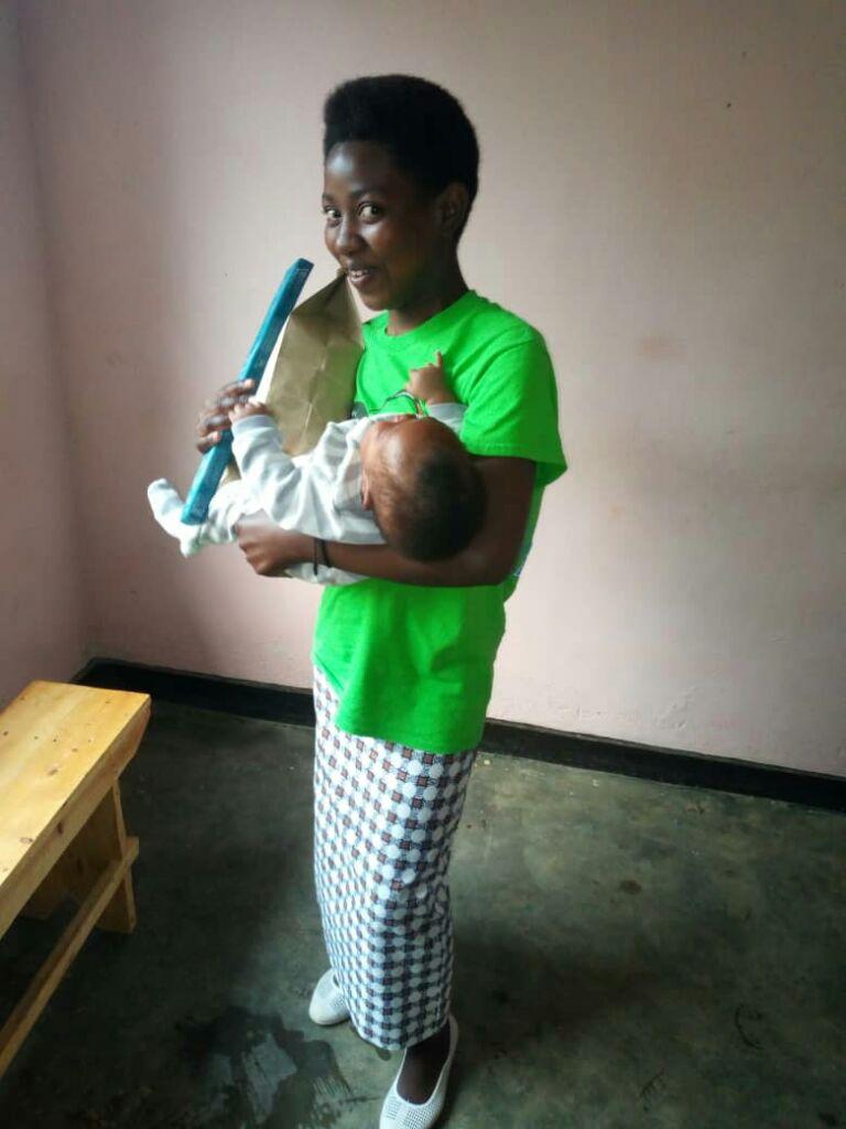 Eine junge Mutter freut sich über das Startpaket.
